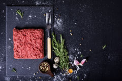 Raw fresh lamb meat, burger patty ingredients. Top view. Raw fresh lamb meat and meat fork on dark background, burger patty ingredients. Top view. Free space Royalty Free Stock Images