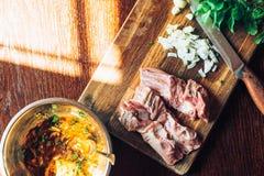 Raw fresh Lamb Meat ribs and seasonings on wooden background. Raw fresh Lamb Meat ribs and seasonings on the wooden background Royalty Free Stock Photography