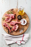 Raw fresh lamb ribs with salt, pepper and cumin on wooden cuttin Stock Photography