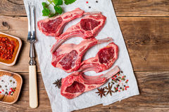 Raw fresh lamb ribs with sauce. Raw fresh lamb ribs with spices on paper on wooden background, top view Royalty Free Stock Photography