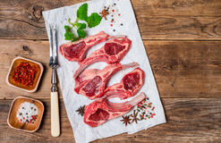 Raw fresh lamb ribs with sauce. Raw fresh lamb ribs with spices on paper on wooden background, top view Royalty Free Stock Photos
