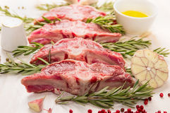 Raw fresh lamb with rosemary and garlic on white wooden background Stock Image