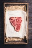 Raw fresh marble T-bone meat on the rustic background. Selective focus. Shallow depth of field royalty free stock photo