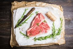 Raw fresh marble T-bone meat on the rustic background. Selective focus. Shallow depth of field stock images