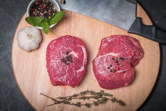 Raw fresh marbled beef Steak. Olive oil, seasonings and knife on wooden cutting board Stock Image