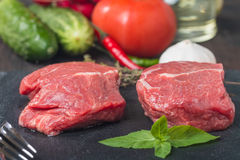 Raw fresh marbled beef Steak. Olive oil, vegetables and seasonings on dark background Royalty Free Stock Images