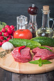 Raw fresh marbled beef Steak. Olive oil, vegetables and seasonings on wooden table Stock Photo