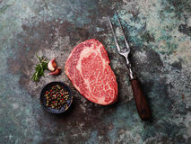 Raw fresh marbled meat Angus Steak. Raw fresh marbled meat Black Angus Steak and seasonings on metal background Royalty Free Stock Photography