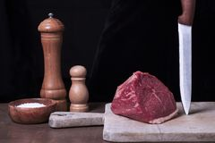 Raw fresh marbled meat Steak filet mignon and seasonings on black background. Ingredients for cooking healthy meat. Dinner on the wooden cutting board Stock Photo