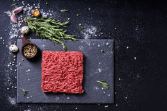 Raw fresh marbled mince meat and seasonings on dark background. Copy space, high angle view Royalty Free Stock Photos