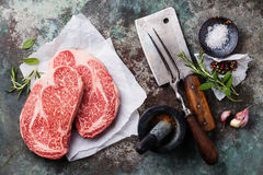 Raw fresh meat Angus Steak. Raw fresh marbled meat Black Angus Steak and seasonings on metal background royalty free stock photos