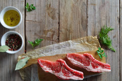 Raw fresh meat. Raw meat for barbecue with fresh vegetables on wooden surface. Food, meat raw steak, beef steak bbq, tomatoes, peppers, spices for cooking meat Stock Images