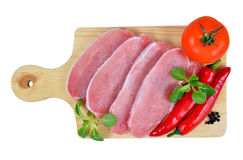 Raw fresh meat with chilli peppers and tomato on board Stock Photo
