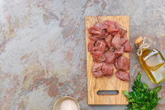 Raw fresh meat on cutting board. Seasoned raw meat ready to be cooked, Top view, blank space on the left side Stock Photos