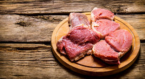 Raw fresh meat on cutting board. On wooden table. Raw fresh meat on cutting board. On a wooden table Royalty Free Stock Images