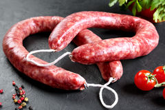 Raw and fresh meat. Fresh sausages and chicken meat ready to cook. Black slate background Royalty Free Stock Photography