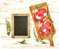 Raw fresh meat with herbs, spices and blackboard. Food backgroun Stock Photo