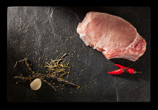 Raw fresh meat with herbs and spices. On stone slate plate Royalty Free Stock Image