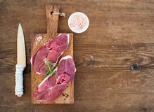 Raw fresh meat lamb entrecote and seasonings on cutting board over rustic wooden background. Royalty Free Stock Images