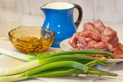 Raw fresh meat,leek and blue pitcher. On white kitchen board Royalty Free Stock Photography