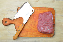 Raw fresh meat and meat cleaver. On light background stock photos
