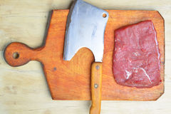 Raw fresh meat and meat cleaver. On light background royalty free stock photos