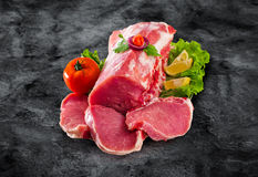 Raw fresh meat medallions with vegetables on black board and cli Stock Image