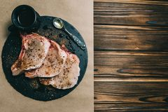 Raw fresh meat pork steak and seasonings on a dark wooden background board honey tomato board royalty free stock images