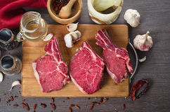Raw fresh meat rib eye steak composition on wooden background Stock Photography