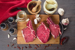 Raw fresh meat rib eye steak composition on wooden background Royalty Free Stock Photography