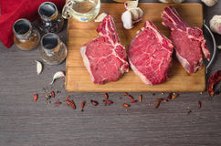 Raw fresh meat rib eye steak composition on wooden background Royalty Free Stock Photos