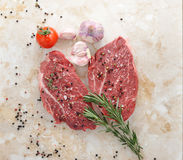 Raw fresh meat Ribeye steak entrecote. Raw beef steak. Steak seasoned with pepper and salt on a marble countertop. Young garlic, cherry tomatoes and rosemary Stock Photos