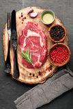 Raw fresh meat Ribeye steak entrecote. Ribeye steak entrecote and seasoning on wooden board Royalty Free Stock Images