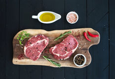 Raw fresh meat Ribeye steak entrecote and seasonings on cutting board. On dark wooden background, top view Stock Image
