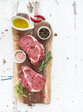 Raw fresh meat Ribeye steak entrecote and seasonings on cutting board over white wooden background. Stock Photos