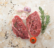 Raw fresh meat Ribeye steak entrecote. And seasonings with pepper and salt on a marble countertop. Young garlic, cherry tomatoes and rosemary. Top view Stock Photography