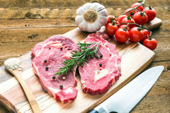 Raw fresh meat Ribeye steak entrecote with vegetables on wooden background. Two fresh ribeye steaks entrecote, garnished a sprig of rosemary, garlic and pepper Stock Photos