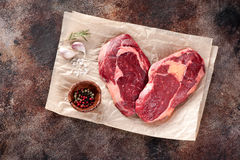Raw fresh meat Ribeye Steak heart shape. Garlic, pepper and rosemary on brown paper Stock Images