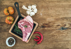 Raw fresh meat ribeye steak with pepper, salt, chili, garlic, heirloom tomatoes and rosemary in cooking pan over rustic Royalty Free Stock Photos