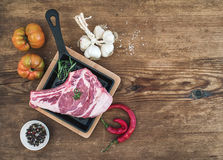 Raw fresh meat ribeye steak with pepper, salt, chili, garlic, spinach, heirloom tomatoes and rosemary in cooking pan. Over rustic wooden background, top view Stock Images