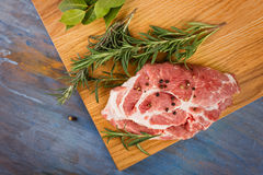 Raw fresh meat ribeye steak and rosemary. On blue background Royalty Free Stock Photo