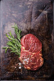 Raw fresh meat Ribeye Steak. And rosemary on dark background Royalty Free Stock Photography
