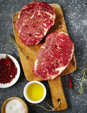 Raw fresh meat Ribeye Steak with rosemary, pepper, salt and olive oil. On stone slate background Royalty Free Stock Photography