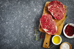 Raw fresh meat Ribeye Steak with rosemary, pepper, salt and olive oil. On stone slate background, top view Royalty Free Stock Images