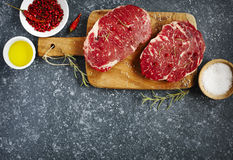 Raw fresh meat Ribeye Steak with rosemary, pepper, sea salt and olive oil. On stone slate background Royalty Free Stock Photos