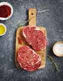 Raw fresh meat Ribeye Steak with rosemary, pepper, sea salt and olive oil. On stone slate background Royalty Free Stock Images