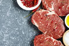 Raw fresh meat Ribeye Steak with rosemary, pepper and sea salt. On stone background, top view Royalty Free Stock Image