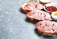 Raw fresh meat Ribeye Steak with rosemary, pepper and sea salt on stone background Stock Photo