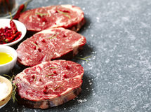 Raw fresh meat Ribeye Steak with rosemary, pepper and sea salt. Stock Photo