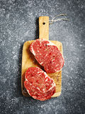 Raw fresh meat Ribeye Steak with rosemary, pepper and sea salt. On stone slate background, top view Stock Photos